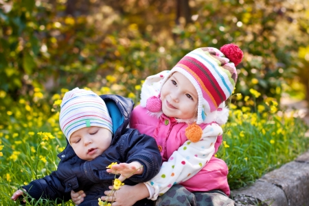 Pretty girl hugging baby brother outdoors in spring  Stock Photo