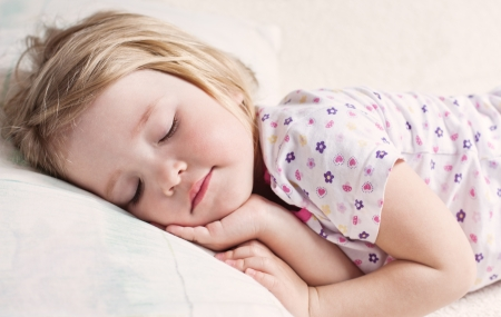 cute little girl sleeping on a bed in her pajamas Stock Photo