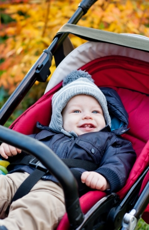 happy baby boy sitting in a red stroller in the autumn park photo