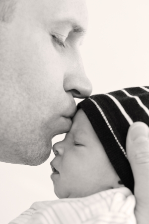 happy father kissing baby son on a white background photo
