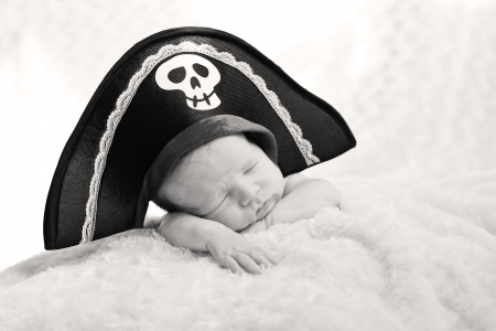 sleeping newborn baby in a pirate hat on a white background photo
