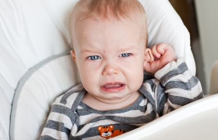 cranky: cute little boy crying and holding his ear on a white background