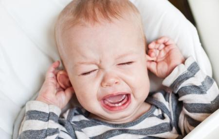 lindo niño pequeño llorando y sosteniendo la oreja sobre un fondo blanco