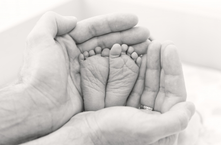 feet newborn baby in father's hands ( black and white )