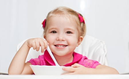 happy little girl eats with a spoon while sitting at table on white background Standard-Bild
