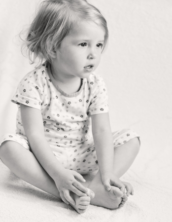 Adorable little girl in pajamas sitting holding hands on their feet   black and white   Stock Photo