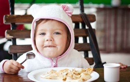 happy toddler girl eating pancakes in outdoor cafe photo