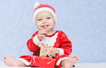 cute baby boy santa helper on a blue background photo