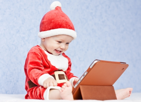 christmas costume: happy santa helper baby boy with digital tablet