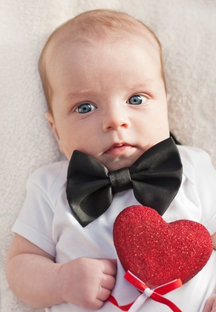charming baby boy gentleman with a heart on a white background Stock Photo - 24097395