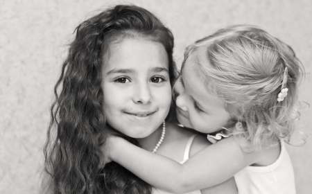 Two beautiful little sisters hugging ( black-white )