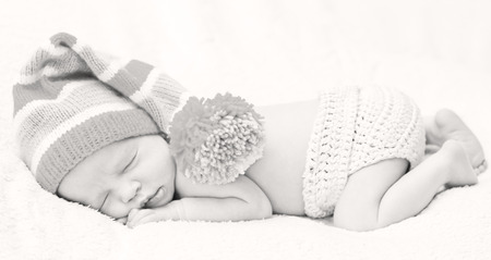 Close-up sleeping newbornon a white background with striped hat (Black and white) photo