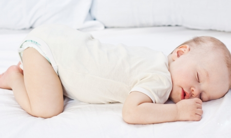 sleeping  funny baby boy on a white  photo