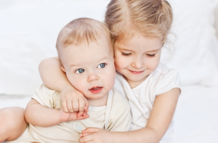 happy little sister hugging her brother on a white background