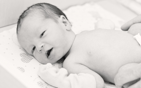 newborn baby in maternity hospital looking at the camera  ( black and white ) photo