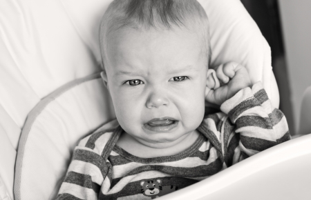 groping: cute little boy crying and holding his ear on a white background ( black and white  )