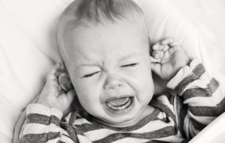 crying child: cute little boy crying and holding his ear on a white background ( black and white  )