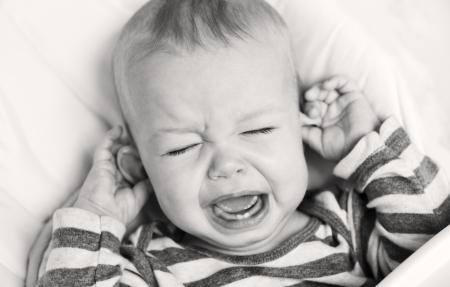 niño llorando: lindo niño llorando y sosteniendo la oreja sobre un fondo blanco (blanco y negro) Foto de archivo