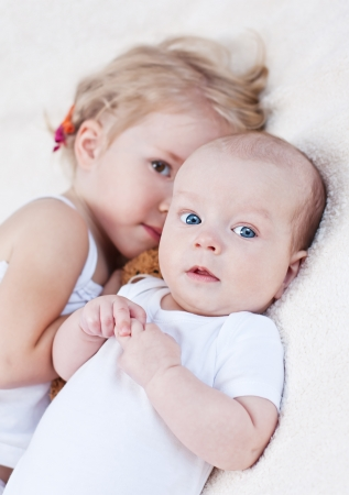 Adorable baby boy and her older sister on a white background Stock Photo