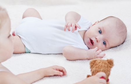 cute baby brother playing toys with sister on a white background