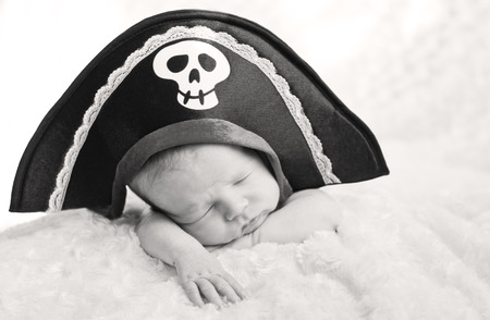 sleeping newborn baby in a pirate hat (soft focus, black and white ) photo