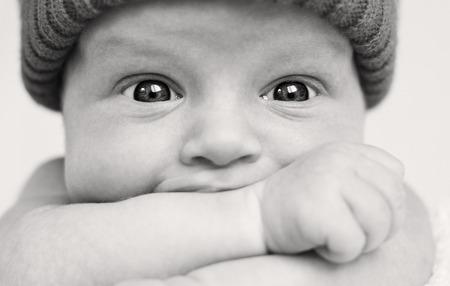 sucks: Cute baby boy with wide eyes funny sucks hand closeup ( black-white )