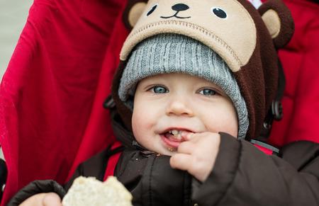 šťastné dítě chlapec sedící v červeném kočárku na procházku Reklamní fotografie