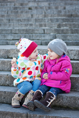 cheerful little girls friends sitting on the stairs