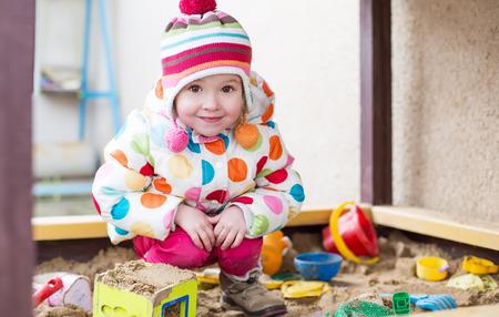 cute little girl in a sandbox  in cold weather Standard-Bild
