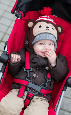 happy baby boy sitting in a red stroller for a walk photo
