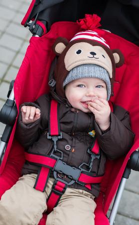 happy baby boy sitting in a red stroller for a walk