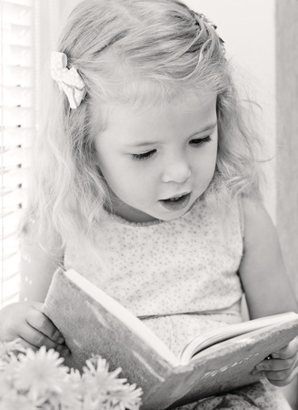 barrettes: Cute little girl reading while sitting on the window ( black and white )