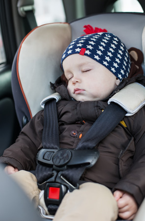 cute baby boy sleeping in car seat photo