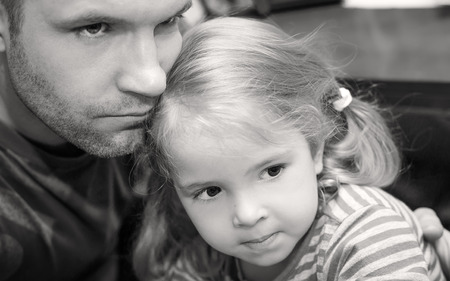 father hugging little daughter calms (black and white) photo