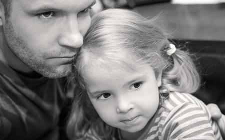 niños pobres: padre abrazando a poco la calma hija (blanco y negro)