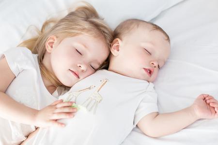 ragazza innamorata: affascinante piccolo fratello e sorella abbraccio addormentato su sfondo bianco