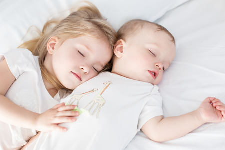 charming little brother and sister asleep embracing on white background photo