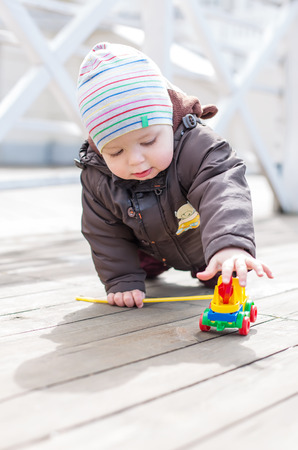 Funny toddler boy crawling and playing with toy outdoors in spring photo
