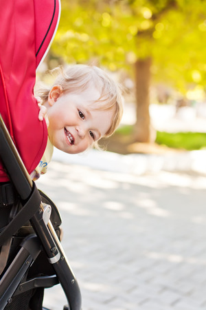 happy baby in a stroller looks out laughing in the park photo