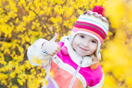 Positive little girl showing a thumbs up on the yellow flowers spring time photo