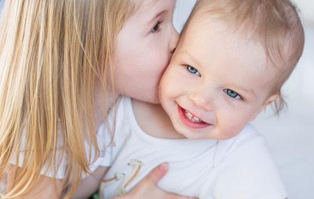 happy little girl hugging kissing his brother