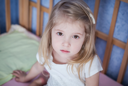 portrait of a little girl sitting in bed Stock Photo
