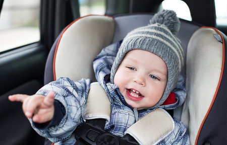 happy toddler  boy sitting in the car seat and shows a rock gesture