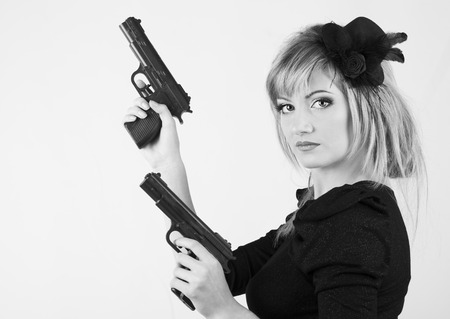 Young woman holding a gun on white background ( black and white ) photo