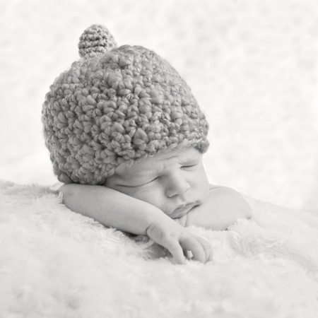 Portrait of a sleeping newborn baby in a knitted hat ( black and white ) photo