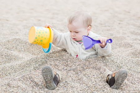 Funny playing at the beach - toddler boy buried in the sand of the beach photo