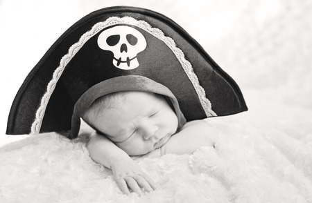 sleeping newborn baby in a pirate hat (soft focus) ( black and white ) photo