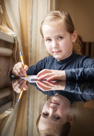 grader: first grader girl writes a pen