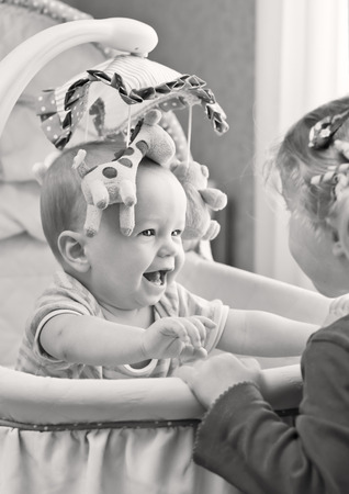Happy baby boy playing with his sister sitting in the cradle ( black and white )