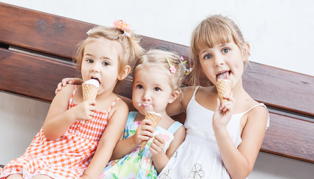 funny children girls eating ice cream sitting on a bench on a white background  photo